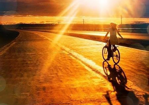 oloi-oi-dromoi-ingolden.gr-woman-bicycle-sunrise-summer-gold-orange-street-way